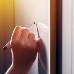 School teacher writing on classroom whiteboard